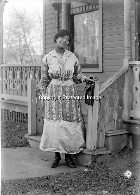 SATIN AND LACE<br /> Fine dressmaking is prominently featured in this portrait of a young woman in a beautiful dress, posing at the steps of a large, Queen Anne style house. Some of the photographs in the collection are scenes of troops training for World War I at the nearby State Fairgrounds. Indeed a number of young men from Lincoln's African American community served in the war. Perhaps the wistful pose of this woman is meant to suggest she is waiting for a letter from a loved one. <br /> <br /> Photographs taken on black and white glass negatives by African American photographer(s) John Johnson and Earl McWilliams from 1910 to 1925 in Lincoln, Nebraska. Douglas Keister has 280 5x7 glass negatives taken by these photographers. Larger scans available on request.