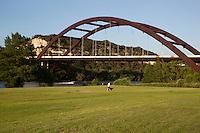 A Ski boat glides under the 360 Bridge on Lake Austin as man walks dog