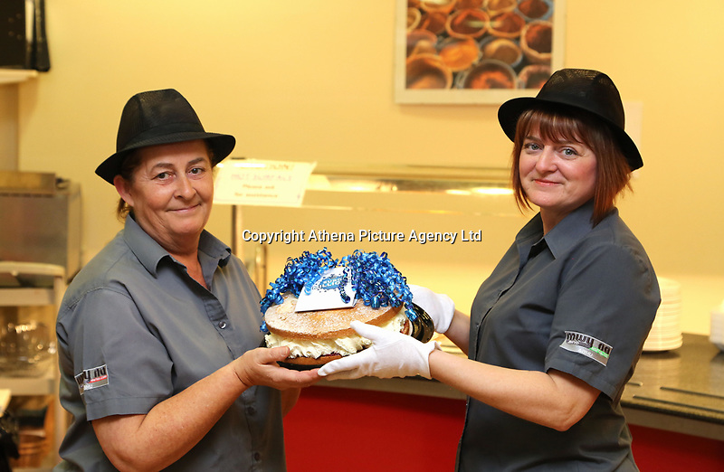 Pictured L-R: Lotto winners colleagues Clare Birchall and Andrea Davies holding a cake for them at Neath Port Talbot hospital. Wednesday 08 November 2017<br />Re: Presentation of hospital catering syndicate win £25m in Euromillions Jackpot at Hensol Castle, south Wales, UK. Julie Saunders, 56, Doreen Thompson, 56, Louise Ward, 37, Jean Cairns, 73, SIan Jones, 54 and Julie Amphlett, 50 all work as catering staff for Neath Port Talbot Hospital in south Wales.