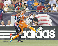 Houston Dynamo forward Cam Weaver (15) controls the ball as New England Revolution midfielder Scott Caldwell (6) pressures. In a Major League Soccer (MLS) match, Houston Dynamo (orange) defeated the New England Revolution (blue), 2-1, at Gillette Stadium on July 13, 2013.