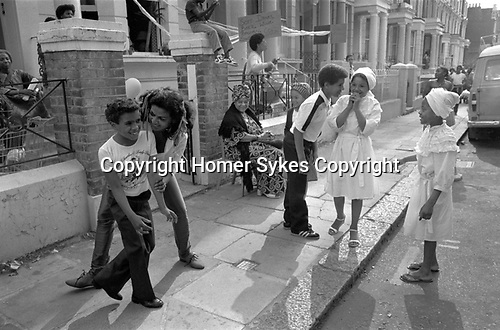 Notting Hill London 1980s UK An older woman with young kid being friendly, other children and adults watching having fun, laughing in the street .During the annual Notting Hill Carnival. 1980s England