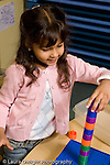 Education Preschool 3-4 year olds girl making tower of stacking pegs vertical