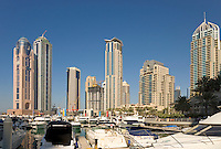 Dubai.  Luxury motor cruisers moored at Dubai Marina with apartment tower blocks in the background...