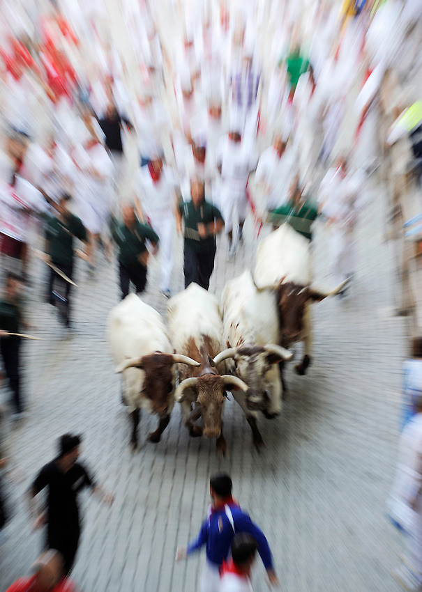 Leading oxes run during the fifth San Fermin Festival´s running of the bulls, on July 11, 2013, in Pamplona, Basque Country. On each day of the eight San Fermin festival days six bulls are released at 8:00 a.m. (0600 GMT) to run from their corral through the narrow, cobbled streets of the old navarre town over an 850-meter (yard) course. Ahead of them are the runners, who try to stay close to the bulls without falling over or being gored. (Ander Gillenea / Bostok Photo)