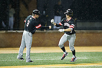 Eric Jones (6) of the Davidson Wildcats taps fists with third base coach Rucker Taylor (3) as he rounds the bases after hitting a home run against the Wake Forest Demon Deacons at David F. Couch Ballpark on February 28, 2017 in Winston-Salem, North Carolina.  The Demon Deacons defeated the Wildcats 13-5.  (Brian Westerholt/Four Seam Images)