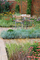 Planting in drifts: Home and garden with patio furniture table and chairs, wooden deck plantings of Achillea, Festuca and other ornamental grasses for xeriscaping dry landscape water-wise plants, brick wall, climbing vines for vertical interest, bistro outdoor table and chairs for dining