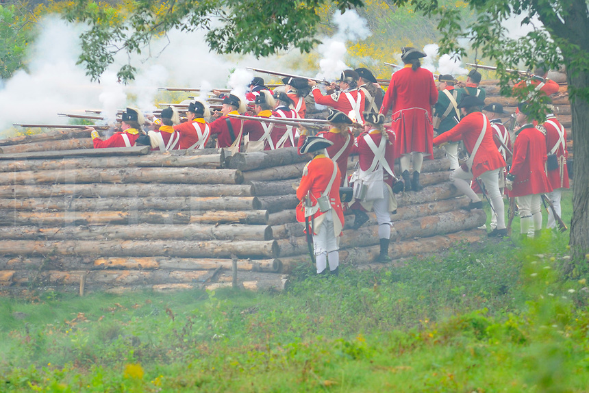 British soldiers fire on the Continental Army from the protection of a log redoubt while defending the Fort during a Revolutionary War re-enactment at Fort Ticonderoga, New York, USA.