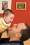 3 month old baby girl with father physical play held up laughing matching expressions vertical Hispanic
