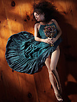 Sensual artistic portrait of a young woman in a green dress with bare legs lying on the floor with closed eyes holding a bouquet of wild flowers Image © MaximImages, License at https://www.maximimages.com