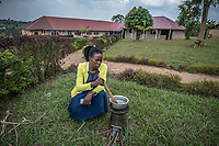 Uganda, Mmanze. Olive Makiremue, headmaster at Christ City School, using her BioLite cook stove that charges light and mobile phones.