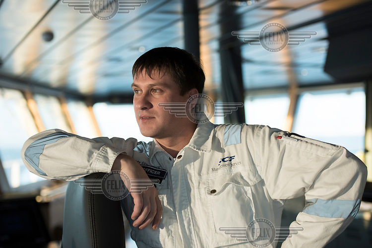Romain, the second officer of the 'Fedor Ushakov' icebraking and supply ship, looks out from the bridge.