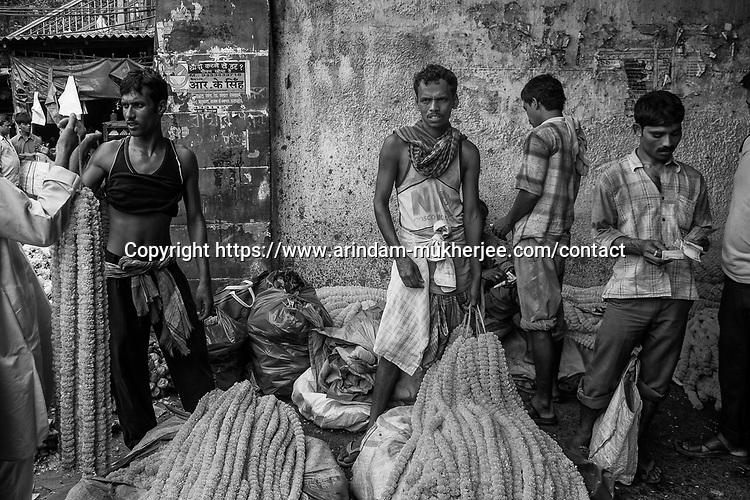 Flower sellers at the wholesale flower market at Jagannath ghat in Kolkata, India.