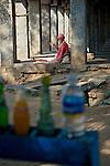 Old indian man with turban sitting in the shade of the colonnade at Hampi Bazar. Hampi, Karnataka, India.