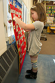 MR / Schenectady, NY. Zoller Elementary School (urban public school). Kindergarten inclusion classroom. Student (girl, 5) selecting activity for learning center time. MR: Cas12. ID: AM-gKw. © Ellen B. Senisi.