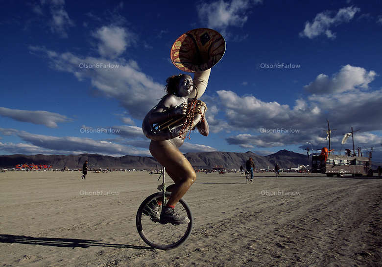 """Wearing a smile and a sousaphone, Erin """"Red"""" Thompson makes music in a balancing act during the annual Burning Man artfest in Nevada's Black Rock Playa. Silver-painted Thompson was like a mirage and disappeared into the crowd on her unicycle. """"There are no spectators,"""" says Red, """"only participants.""""  The counter-culture celebration is held in the desert annually."""