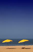 Two beach umbrellas sit on beach