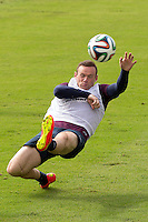 Wayne Rooney of England dives for a ball during training