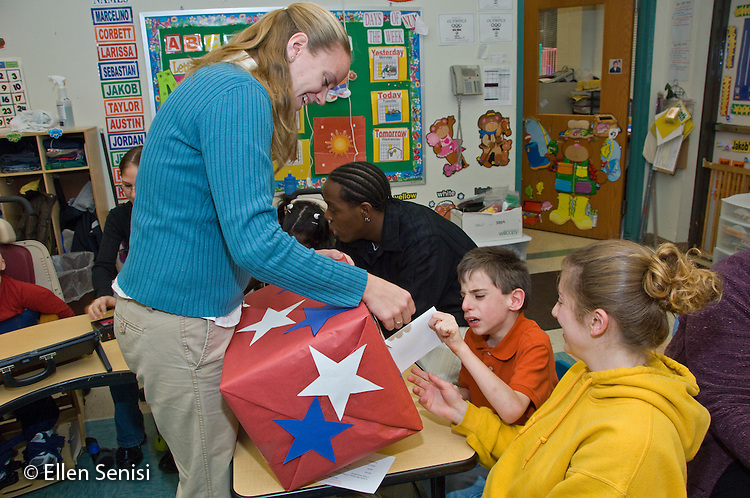 MR / Albany, NY.Langan School at Center for Disability Services .Ungraded private school which serves individuals with multiple disabilities.Teaching assistant helps boy put envelope in box (helped by Special Education teacher) to cast vote during speech and language development lesson. This action gives him practice in grasping and coordination, both of which are helpful for his condition.  Boy: 9, cerebral palsy.MR: Cam10, Mye2, Ris4.© Ellen B. Senisi