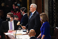 Speaker of the United States House of Representatives Nancy Pelosi (Democrat of California) and US Vice President Mike Pence preside over the Electoral College vote certification for President-elect Joe Biden, during a joint session of Congress at the U.S. Capitol in Washington, DC on Wednesday, January 6, 2021.<br /> CAP/MPI/RS<br /> ©RS/MPI/Capital Pictures