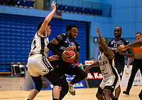 Tony Hicks of Surrey Scorchers battles between Louis Sayers of Newcastle Eagles and Rahmon Fletcher of Newcastle Eagles during the BBL Championship match between Surrey Scorchers and Newcastle Eagles at Surrey Sports Park, Guildford, England on 20 March 2021. Photo by Liam McAvoy.