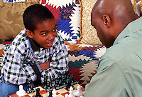 An African-American father plays chess with his son at home.