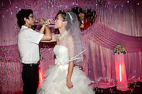 At a wedding party Zeng Zhongzhong (bridegroom) and Jiang Xiaoxiao (bride) link arms to share a symbolic matrimonial toast. Wedding receptions are an important part of the The West Lake Restaurant's business with several taking place there each Saturday night. Able to seat up to 5,000 people at one sitting, The West Lake Restaurant is the biggest Chinese restaurant in the world. Each week its diners, who staff are taught are 'the bringers of good fortune', devour 700 chickens, 200 snakes, 1,200 kgs of pork and 1,000 kgs of chillis. Its 300 chefs cook in five kitchens and its staff total more than 1,000.It is fully booked most nights.