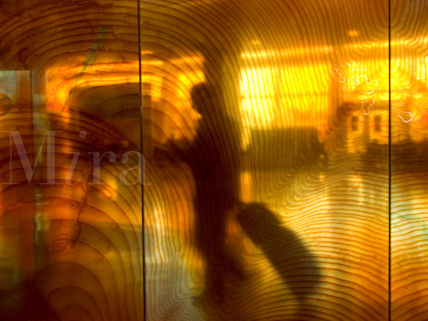 Blurred motion through colored glass of people walking with luggage at SeaTac airport Seattle Washington US