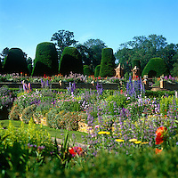 Colourful flowerbeds fill the extensive grounds of Packwood House, while stately topiary yews dominate another garden beyond