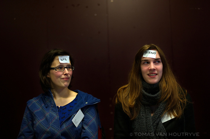 Women play a game with Dutch words stuck to their heads during training for flemish youth leaders in Brussels, Belgium on March 3, 2013. Flemish government policy imposes that only the Dutch language can be used during any activities supported by the government. Youth leaders receive special training to communicate with non-Dutch speakers without using French.