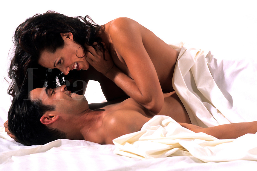 Sexy couple in bed romance under sheets snuggling.