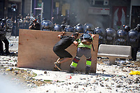 Rioters advance toward a police lines using a cardboar as a shield during severe clashes   near the Congress building while Deputies Chamber was   discussing changes in   retirement legislation