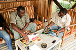 Gabonese field assistants looking through National Geographic magazine, Lope National Park, Gabon