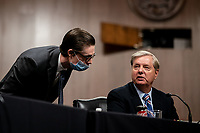 United States Senator Lindsey Graham (Republican of South  Carolina), Chairman, US Senate Judiciary Committee confers with an unidentified aide during a US Senate Judiciary Committee business meeting to consider authorization for subpoenas relating to the Crossfire Hurricane investigation and other matters on Capitol Hill in Washington, DC on June 11, 2020.<br /> Credit: Erin Schaff / Pool via CNP/AdMedia