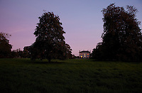 The illuminated windows of Burtown House glimmer across the darkening park against the evening sky