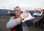 Rangers supporter tears up his season ticket renewal form as Rangers fans stage a demo at Ibrox Stadium this afternoon