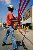 Underground fiber optic cable conduit installation in business district right of way, Los Angeles, CA. Communications, job, career, blue collar worker, safety helmet. Hard hat worker. Los Angeles California.
