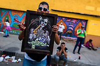 "A Mexican worshipper of Santa Muerte (Holy Death) holds a ""Bandida"" (a female bandit) artwork during a religious pilgrimage in Tepito, a rough neighborhood of Mexico City, Mexico, 1 April 2018. The religious cult of Santa Muerte is a fusion of Aztec death worship rituals and Catholic beliefs. Born in lower-class neighborhoods of Mexico City, it has always been closely associated with crime. In the past decades, original Santa Muerte followers, such as prostitutes, pickpockets and street drug traffickers, have merged with thousands of ordinary Mexican Catholics. The Holy Death veneration, offering a spiritual way out of hardship in modern society, rapidly expanded. Although the Catholic Church still considers Santa Muerte followers the devil worshippers, on the first day of every month, crowds of Santa Muerte believers fill the streets of Tepito. Holding statues of Holy Death clothed in a long robe, they pray for healing, protection, money or any other favor in life."