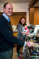 A woman stirs as saucepan of soup and breastfeeds her 20 month old toddler at the same time.  The toddler is sitting on the kitchen work top. Her husband is cooking too in the foreground.<br /> <br /> 07/02/2013<br /> Hampshire, England, UK
