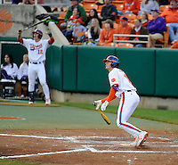 Jon McGibbon (12), left, is already celebrating as designated hitter Shane Kennedy (11) of the Clemson Tigers watches his game-winning two-run home run head to the left-center stands in the bottom of the eighth inning in a game against the William & Mary Tribe on Opening Day, Friday, February 15, 2013, at Doug Kingsmore Stadium in Clemson, South Carolina. Clemson won, 2-0. (Tom Priddy/Four Seam Images)
