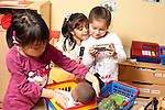 Education Preschool Headstart girls in family kitchen area one girl tucking doll into basket two girls looking at camera pretending to view photo