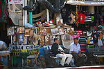 TWO MEN SIT OUTSIDE MEXICAN SOUVENIR SHOP