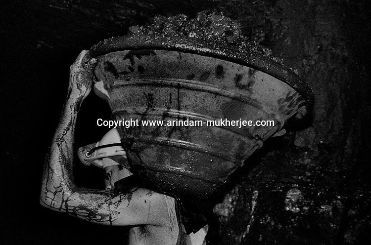 A miner carrying a  bucket of coal on his shoulder. Ranigunj, West Bengal, India. Arindam Mukherjee