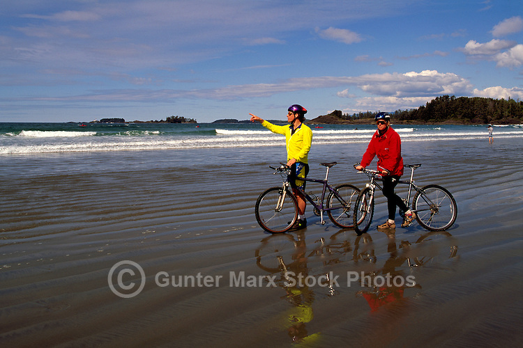 West Coast, Vancouver Island, BC, British Columbia, Canada - Young Couple mountain biking on Beach near Tofino, Summer (Model Released)