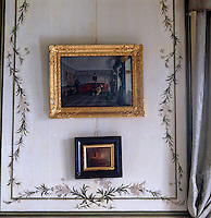 Two paintings hang against a hand-painted wall panel in this bedroom
