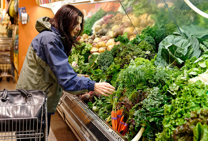Woman shopping for fresh organic produce in a heath food grocery store.