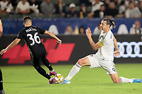 CARSON, CA - SEPTEMBER 15: Zlatan Ibrahimovic #9 of the Los Angeles Galaxy and Luis Martins #36 of Sporting Kansas City battle for a loose ball during a game between Sporting Kansas City and Los Angeles Galaxy at Dignity Health Sports Complex on September 15, 2019 in Carson, California.