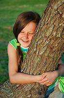 Girl hugging a tree.