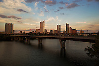 A warm sunset greets the sparse Austin Skyline over the Town Lake Pedestrian Bridge as runners and joggers cross Town Lake.