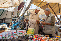 Morocco.  Completing a Purchase: Rat Poison and Insecticide, Had Draa Market, Essaouira Province.