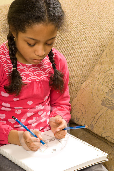 10 year old girl sitting on couch at home art activity sketching with pencil